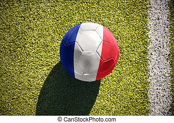 football ball with the national flag of france lies on the field