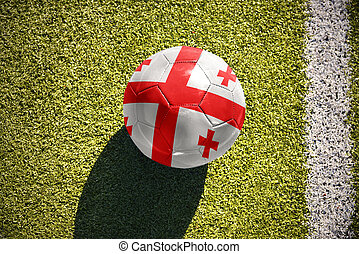 football ball with the national flag of georgia lies on the field