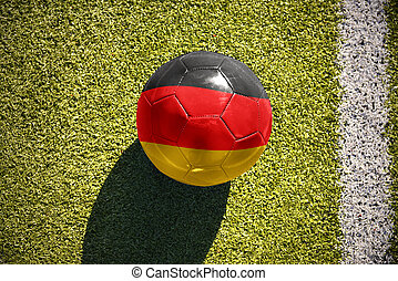 football ball with the national flag of germany lies on the field