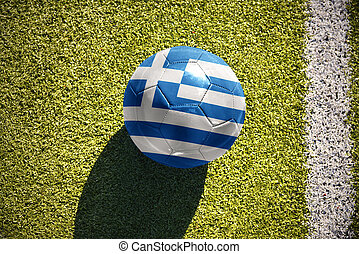 football ball with the national flag of greece lies on the field