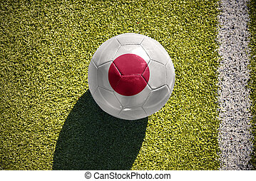 football ball with the national flag of japan lies on the field