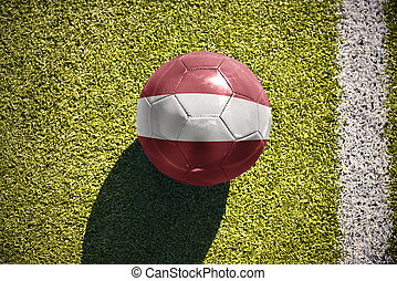 football ball with the national flag of latvia lies on the field