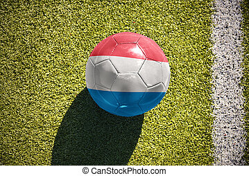 football ball with the national flag of luxembourg lies on the field
