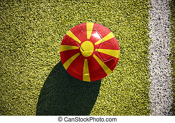 football ball with the national flag of macedonia lies on the field