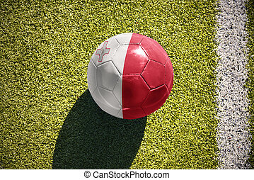 football ball with the national flag of malta lies on the field