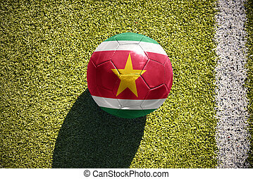 football ball with the national flag of suriname lies on the field