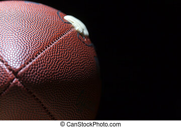 Football - close up of an american football against a black ...