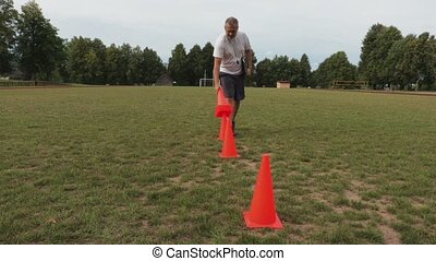 Football coach collects the cones from the field