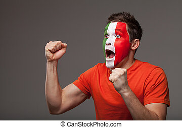 Football fan is rooting. With painted Italian flag on a face