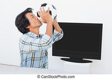 Football fan kissing ball against tv