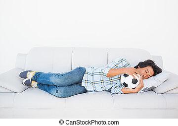 Football fan sleeping on couch hugging ball