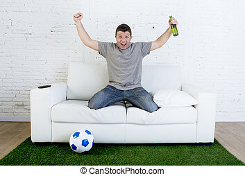 football fan watching tv match on sofa with grass pitch carpet celebrating goal