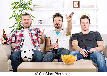 Football fans - Excited young men are watching football at...