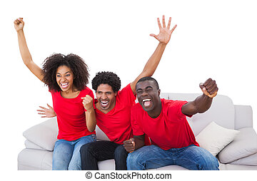Football fans in red cheering on the sofa on white ...