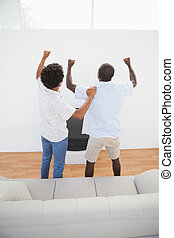 Football fans standing and cheering in front of tv