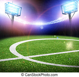 Football field on a stadium with lights and flashes at night