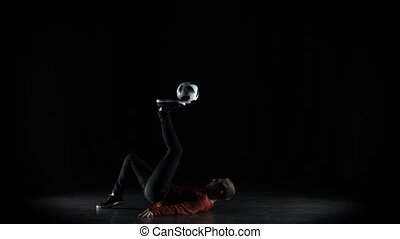 Football freestyler practices with soccer ball at dark...