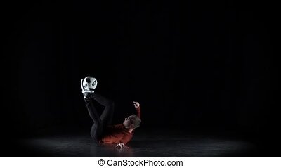 Football freestyler practices with soccer ball while doing...