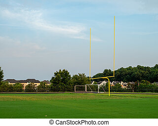 Football goal post at a high school field in the evening sun