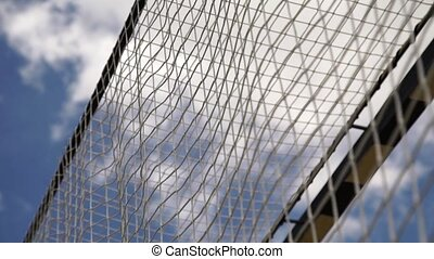 Football is flying in the goal on cloudy sky background