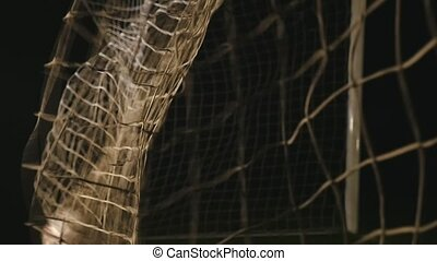 Football is flying into the gate net in the black background in slow motion