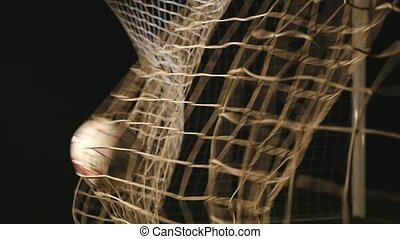 Football is soaring into the goal net in the black...