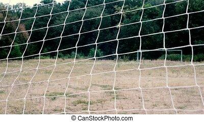 football net. football grid. view through the football net on the opposite gate. rural football field
