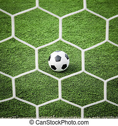 football on green grass in front of the net