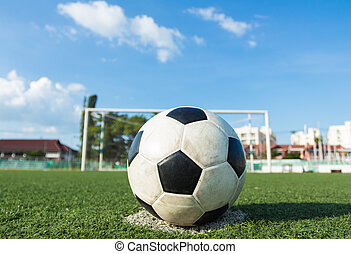 football on green grass with goal