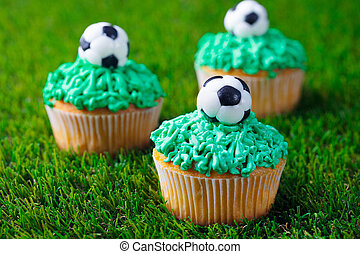 Football party, birthday decorated cupcake on green grass background. Close up.