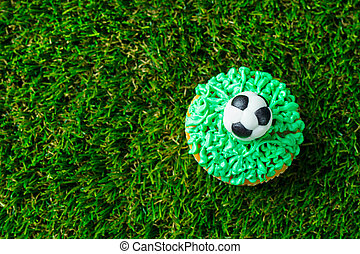 Football party, birthday decorated cupcake on green grass background. Copy space. Top view.