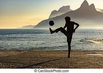 football plage, à, coucher soleil