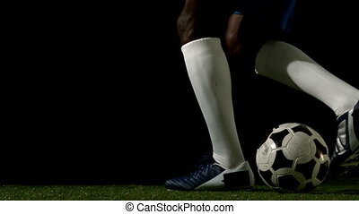Football player controlling the ball on grass in slow motion