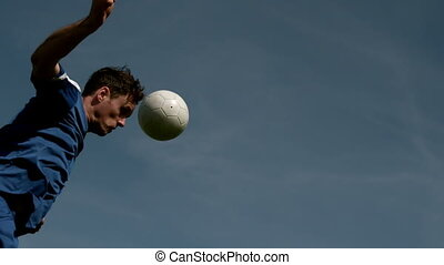 Football player heading the ball under blue sky in slow...