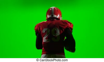 Football player holding the ball in hand and run with it. Green screen