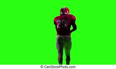 Football player in a red helmet and sports gear runs with the ball. Green screen. Back view
