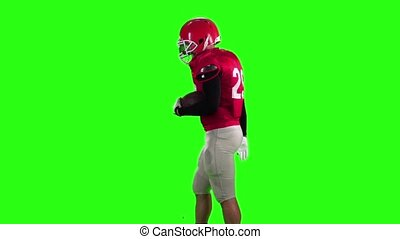Football player in a red helmet comes with a ball. Slow motion, green screen,