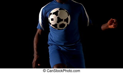 Football player in blue controlling the ball in slow motion