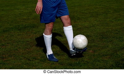 Football player in blue controlling the ball on pitch in...