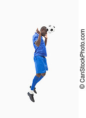 Football player in blue heading the ball