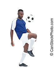 Football player in blue jersey controlling ball on white...