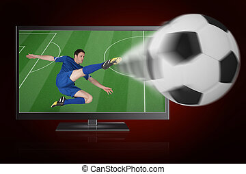 Football player in blue kicking ball out of tv against red background with vignette