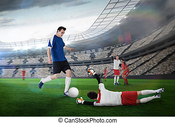 Football player in blue kicking against large football...
