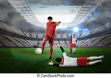 Football player in red kicking against large football...