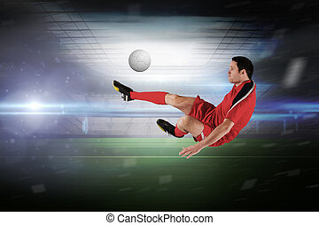 Football player in red kicking in a large football stadium...