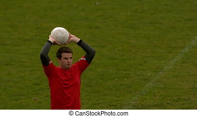 Football player in red throwing the ball