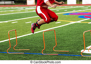 Football player jumping over orange hurdles,