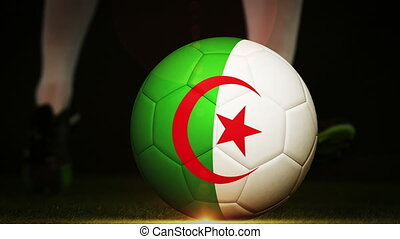 Football player kicking algeria flag ball on black...
