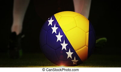 Football player kicking bosnia flag