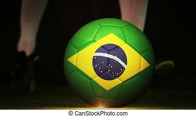 Football player kicking brazil flag ball on black background...